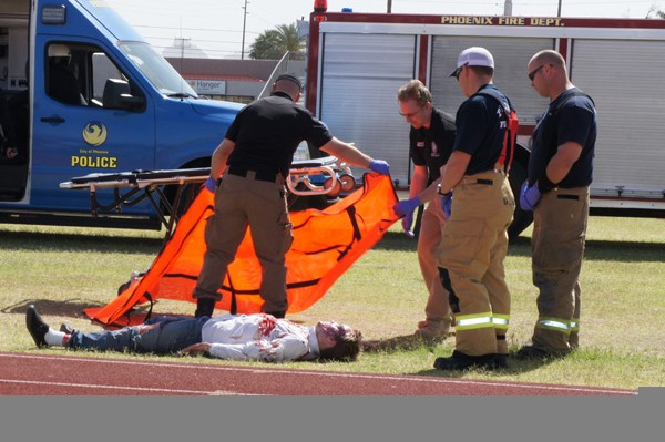 Central High drama student Richard Jenkins, who was ejected through the windshield and died at the scene of the mock DUI demonstration, is loaded into a body bag by Phoenix firefighters and members of the Maricopa County coroner's office.